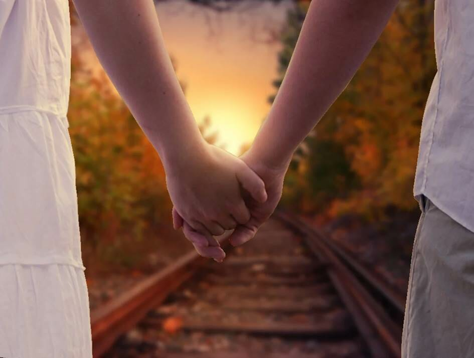 Man and woman holding hands on train tracks