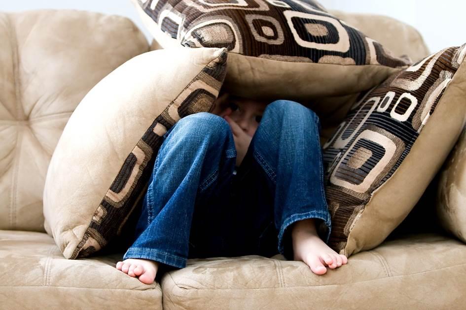 Boy hiding behind cushions