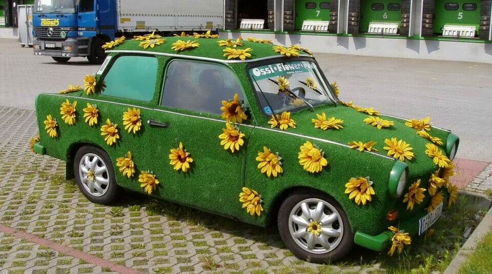 Car covered in grass and sunflowers