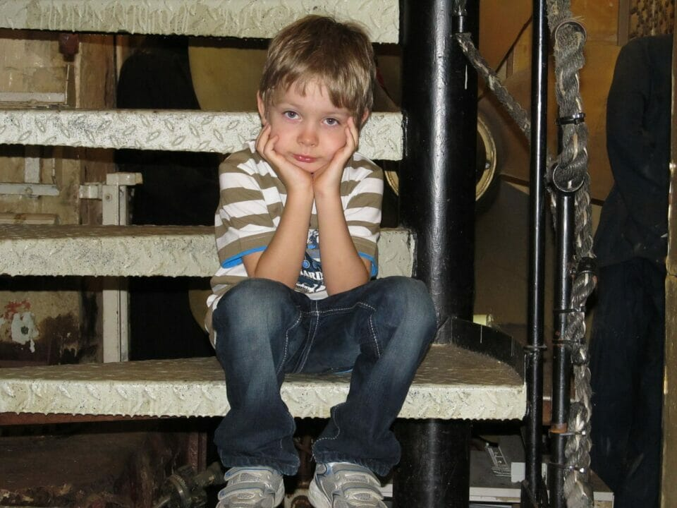 Boy posing impatiently on spiral stairs