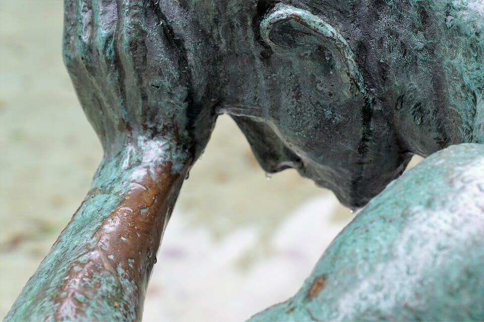 Bronze sculpture of man holding his head