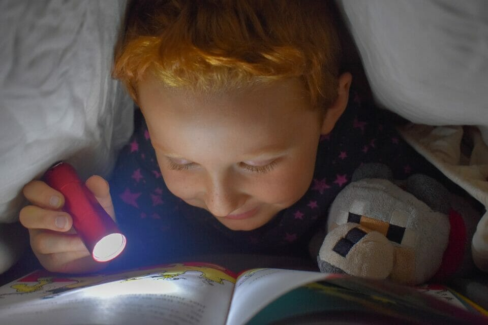 Kid reading a book under a blanket with a flashlight