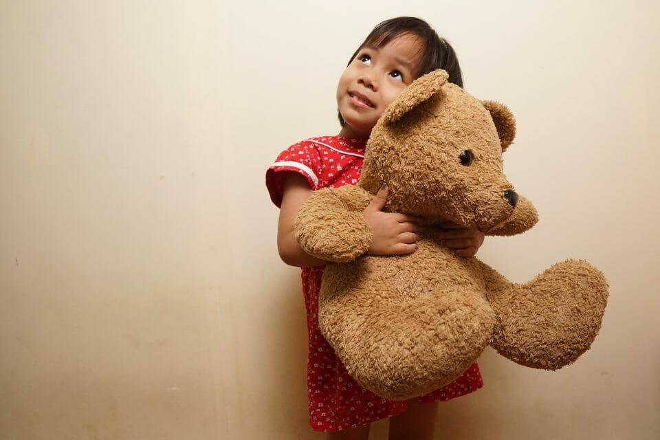 Bored little girl holding a big teddy bear