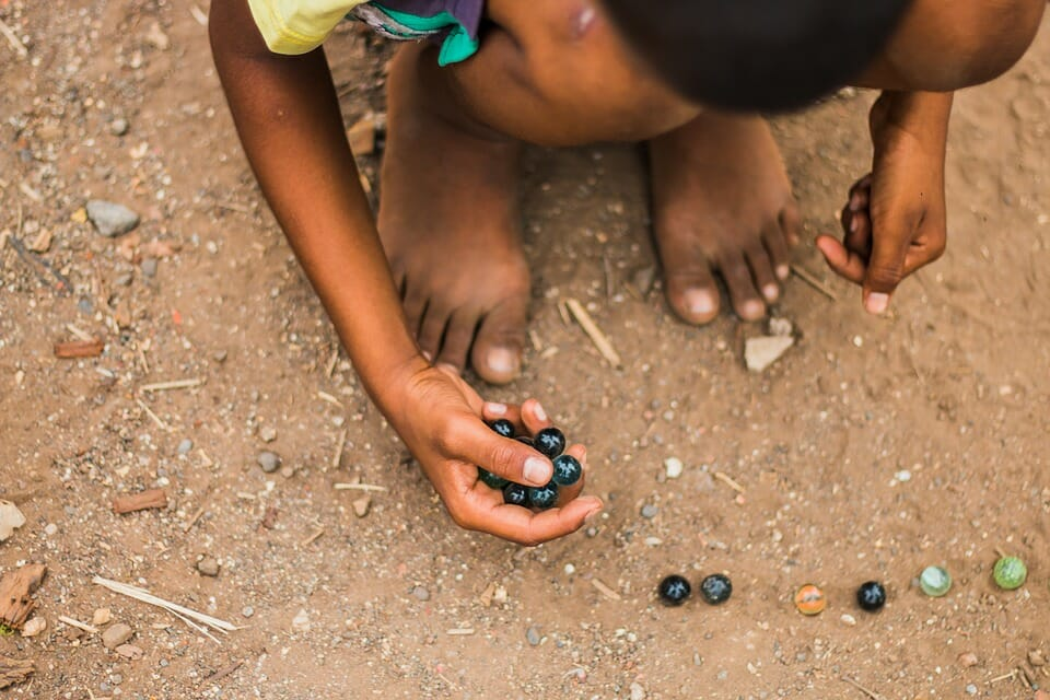 Boy playing marbles in the dirt