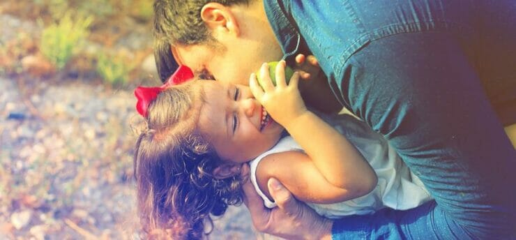 Father kissing giggling daughter