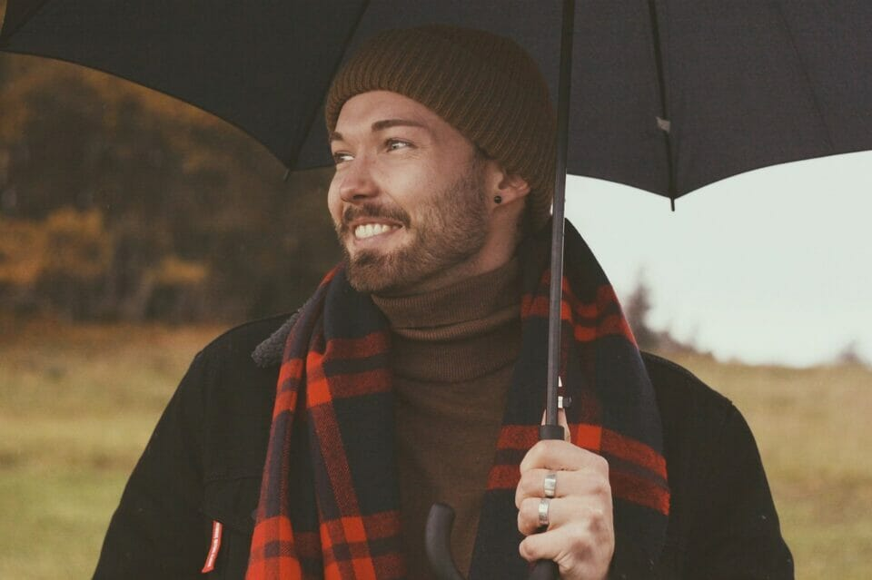 Man smiling happily under umbrella