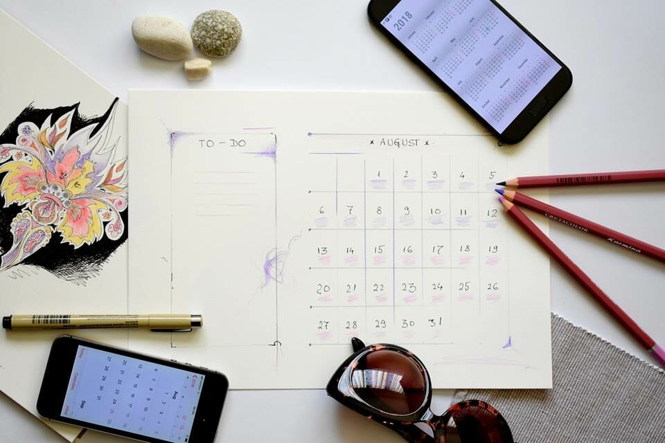 August calendar, sunglasses and mobile phones - planning the holidays