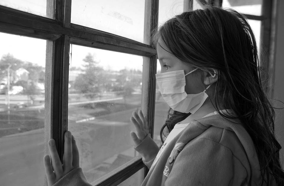 Girl in surgical mask looking sadly out the window