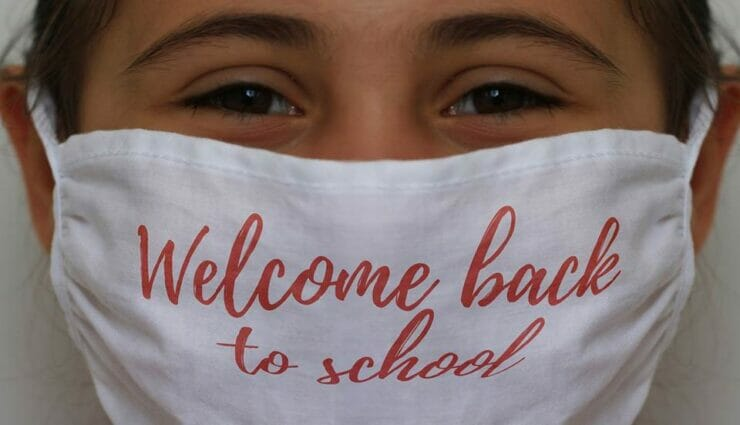 Girl with mask saying 'Welcome back to school'