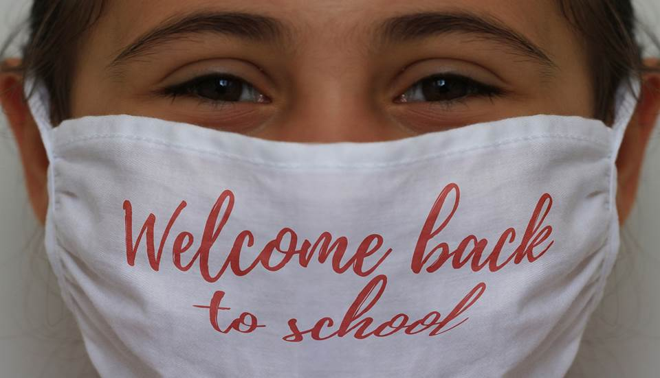 Girl with mask saying'Welcome back to school'