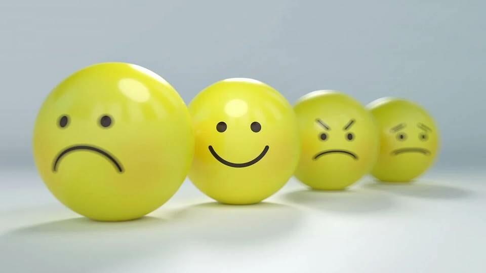 Smiling yellow ball among frowning or sad balls