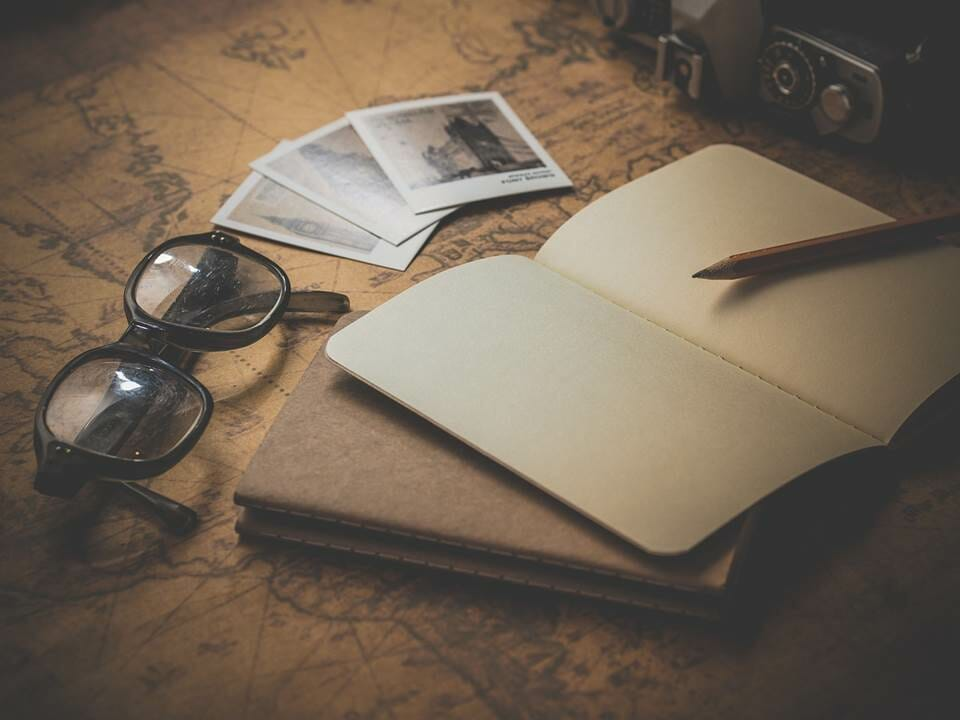 Passport, travel photos, camera and glasses on a world map