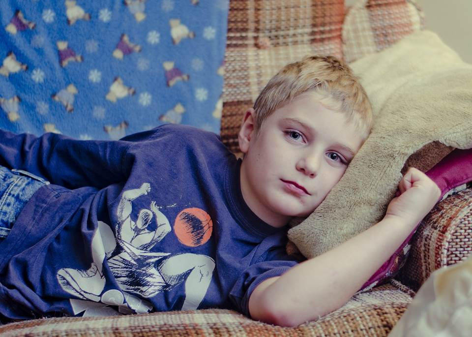 Boy lying on the couch looking bored