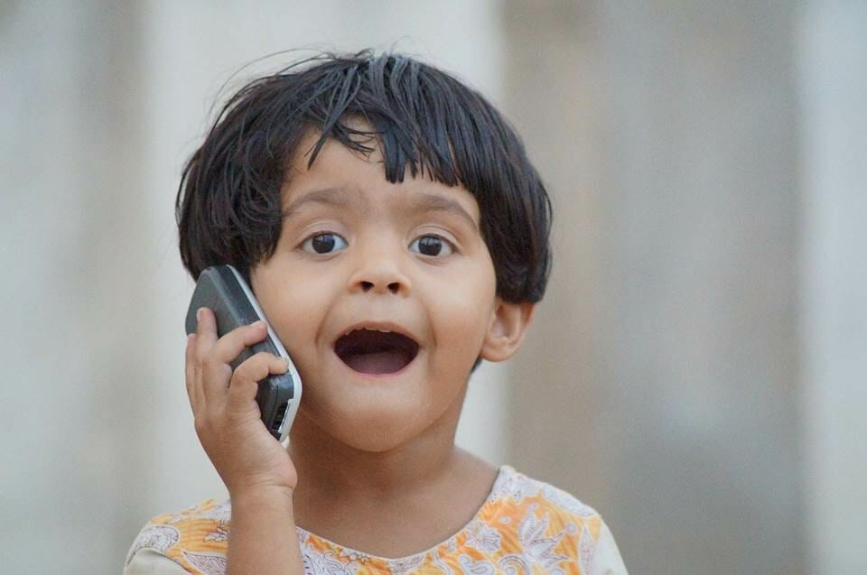 Young girl excited to be heard on the phone