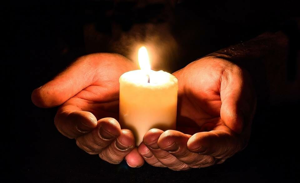 Hands holding a candle to light the dark