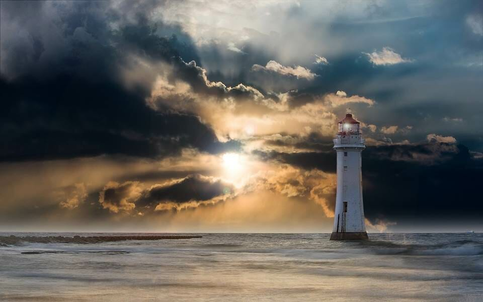 Rays of sun light shining through clouds on a lighthouse and the ocean