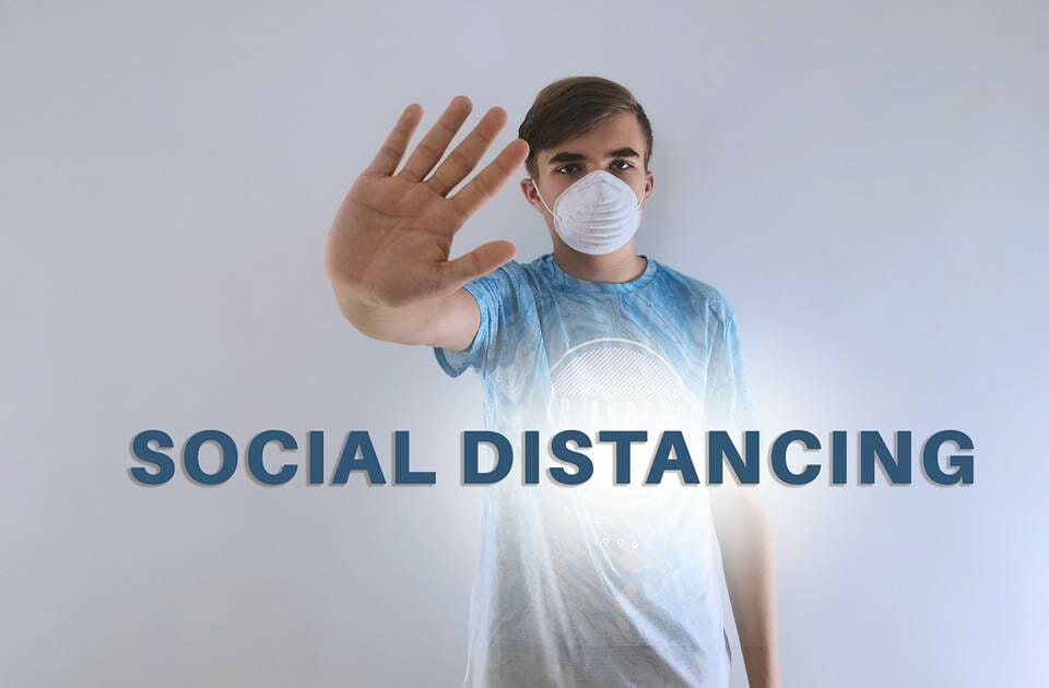 Masked teenage boy holding out his hand for Social Distancing