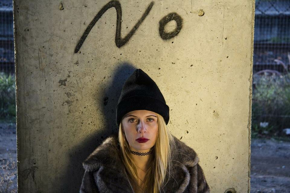"""Woman sitting in front of the word """"No"""" sprayed on a wall"""