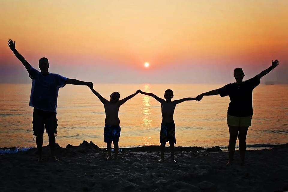 Family holding hands on the beach at sunset