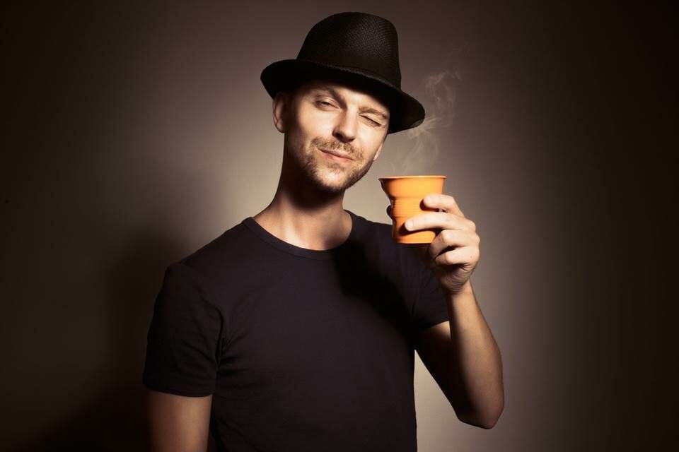 Man holding a steaming cup of coffee happily