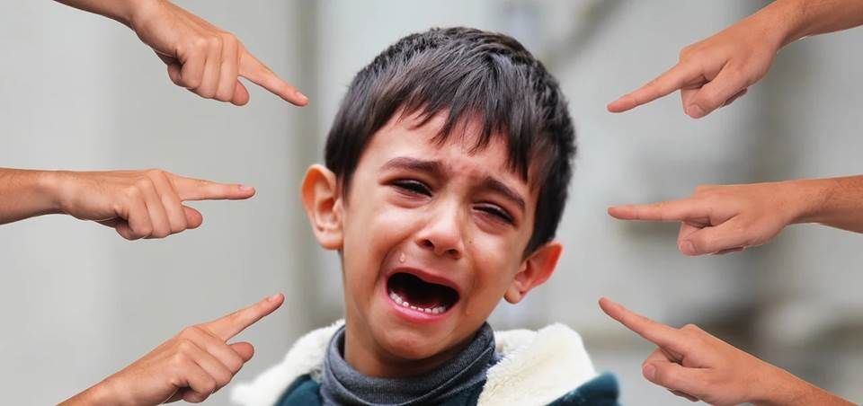 Boy crying surrounded by pointing fingers