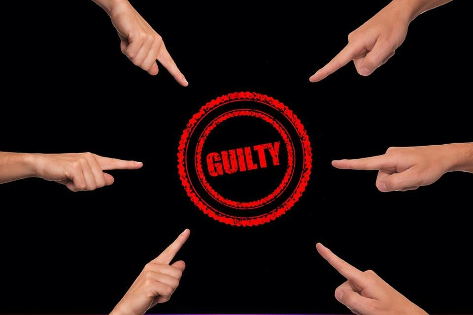 "Fingers pointing to the word ""guilty"""
