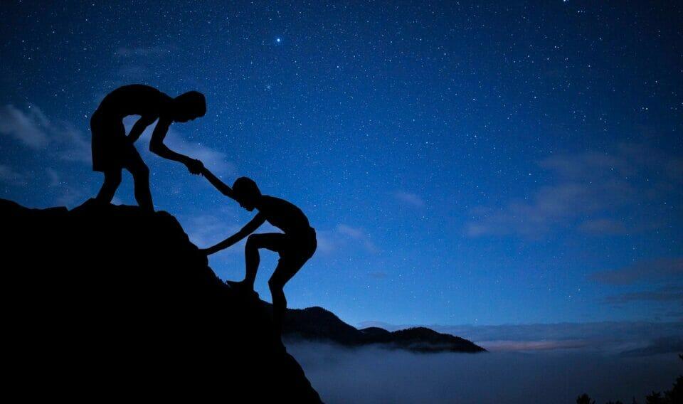 Boy helping another boy climb a mountain
