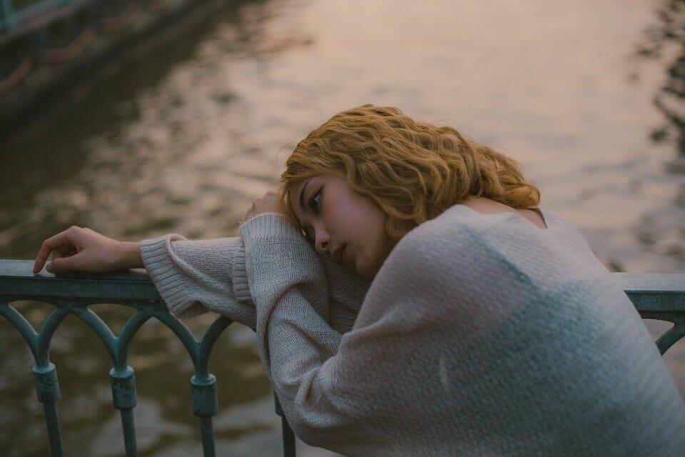 Teen girl leaning hopefully against a railing