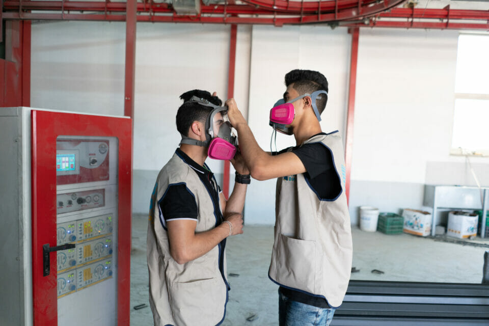 Young man wearing gas mask helping another with his mask