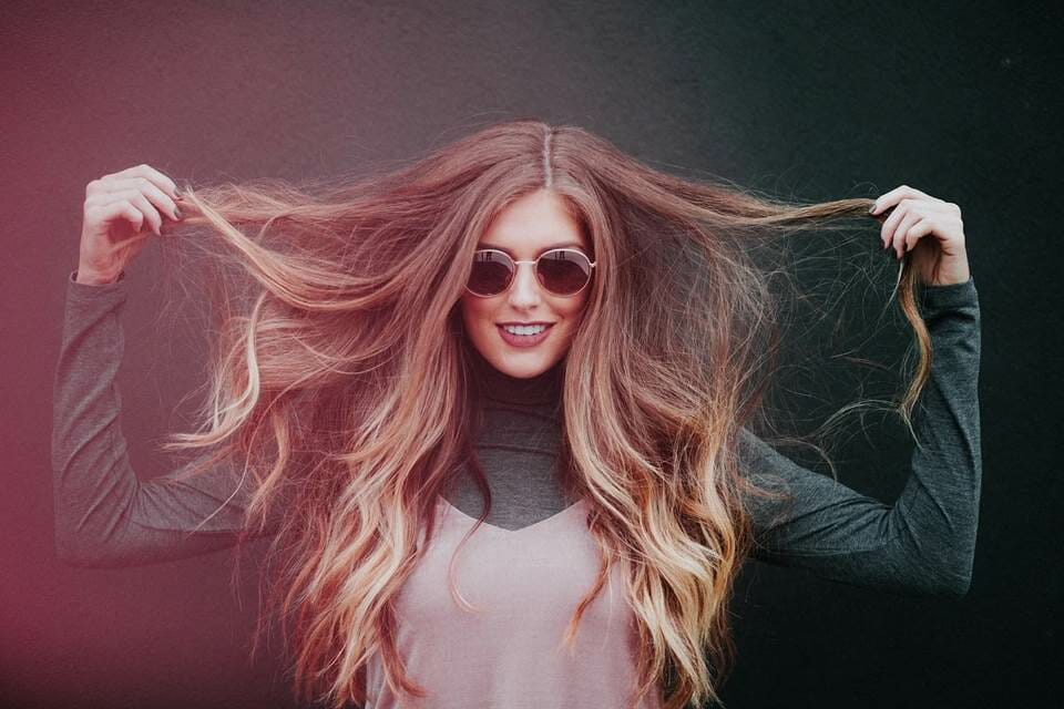 Woman holding her hair to the sides and smiling